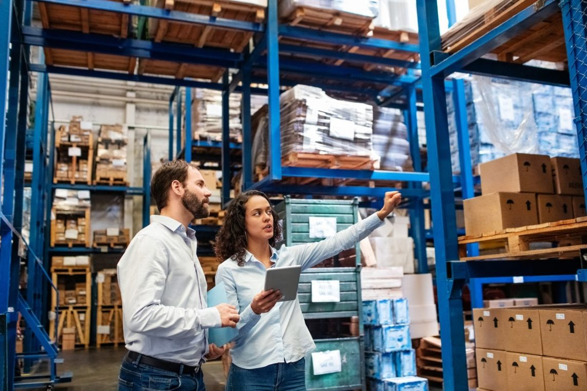 a warehouse manager discusses logistics with a colleague