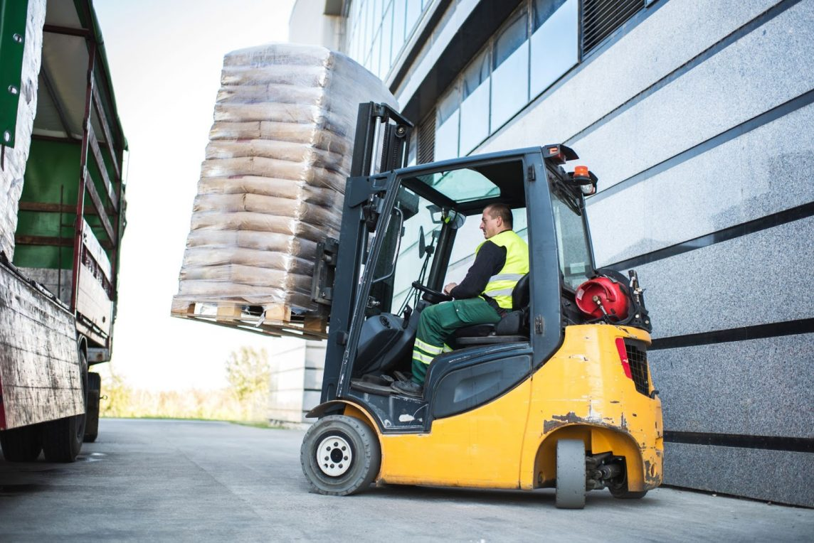 forklift operator using a forklift to load a pallet onto a truck