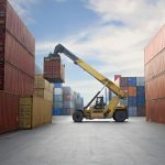 a crane lifting up a cargo container in a port