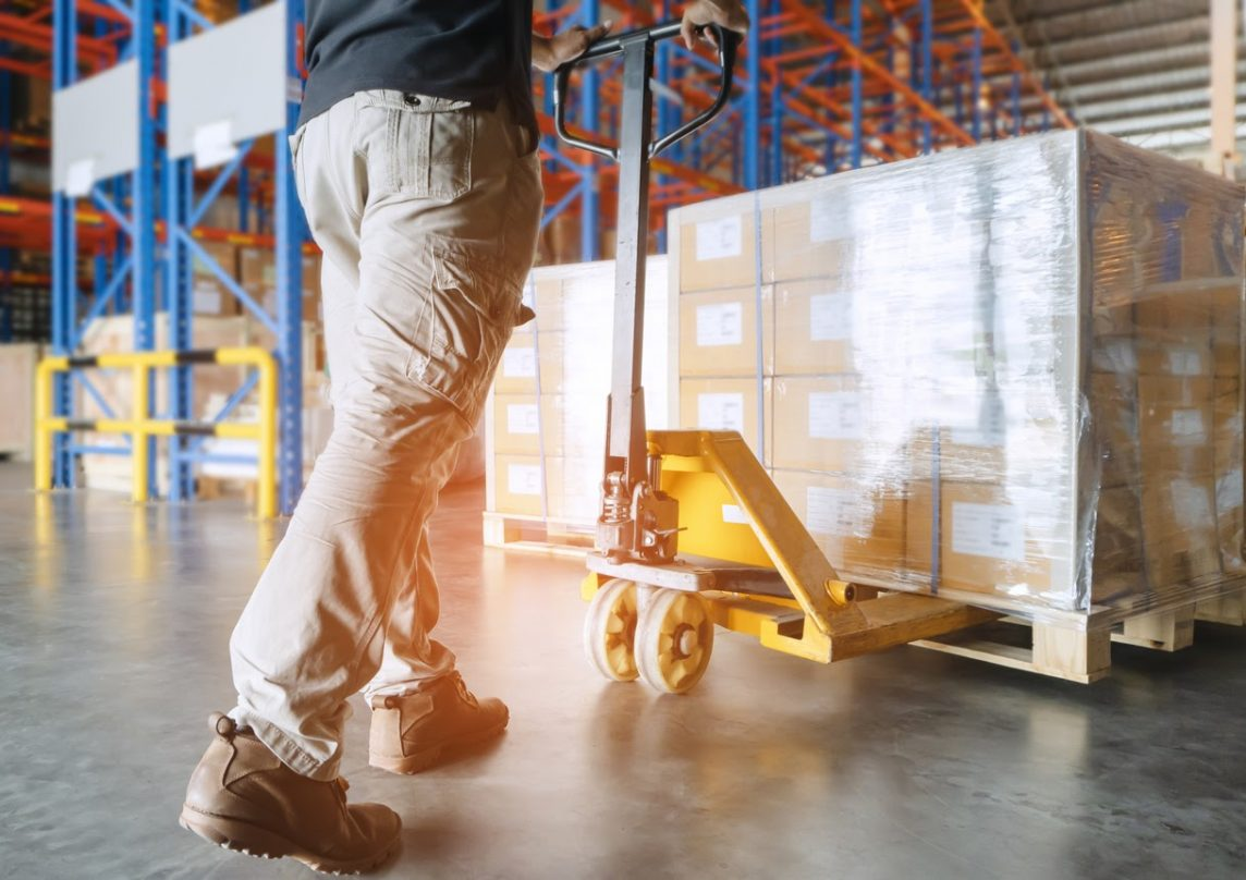 A warehouse staff member moving a pallet using a jack.